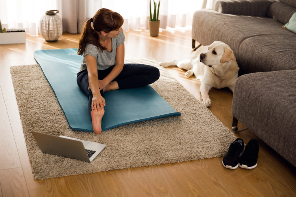 Woman doing physiotherapy in her home with dog watching
