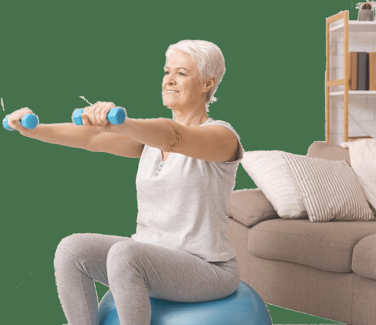 Eldre dame sitter på gymball og trener hjemme i stue